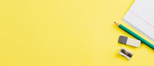 Cahier avec un crayon sur fond jaune.