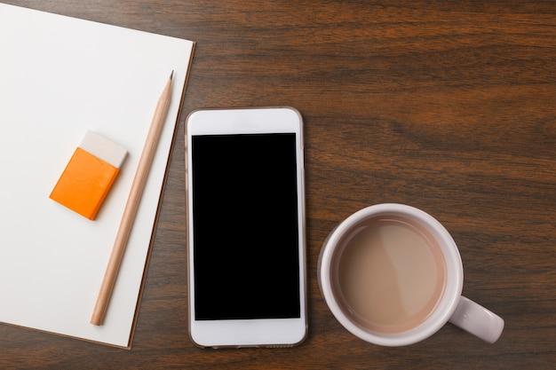 Cahier, crayon, gomme à effacer, téléphone et boisson chaude sur le bureau en bois