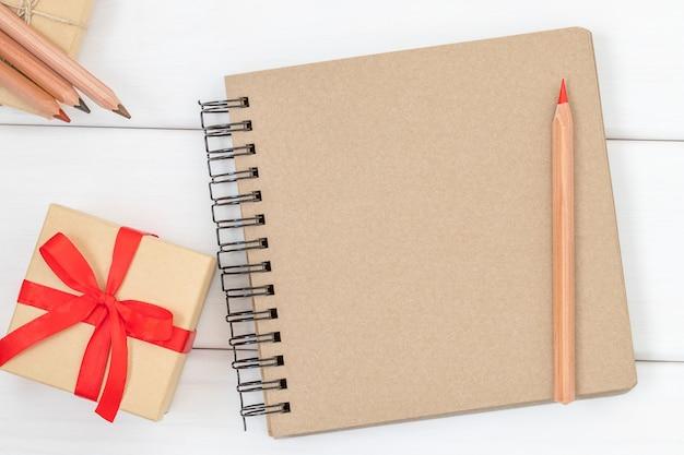 Cahier avec crayon rouge et boîte-cadeau sur bois blanc