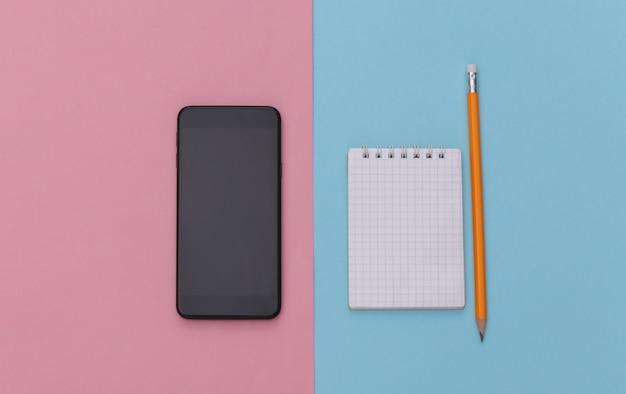 Cahier avec crayon, smartphone sur fond bleu rose. vue de dessus