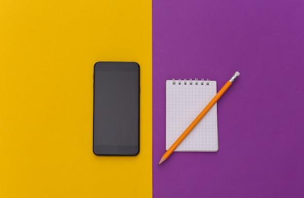 Cahier avec crayon, smartphone sur fond jaune violet. vue de dessus