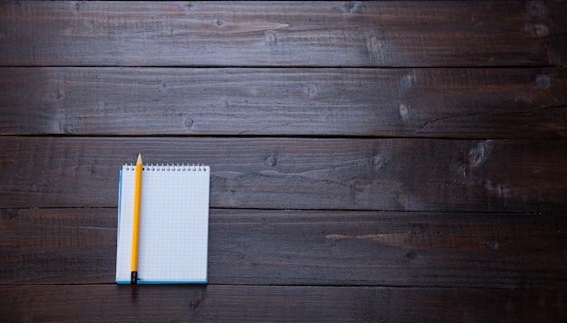 Cahier et un crayon sur une table en bois.