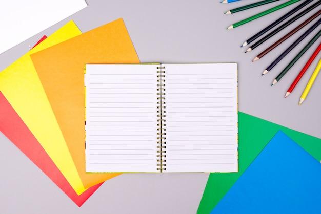 Cahier avec des crayons de couleur et du papier de couleur sur gris