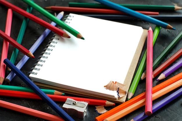 Cahier à dessin et crayons de couleur sur fond sombre