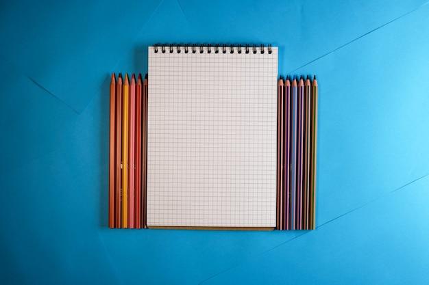 Cahier détachable avec des crayons de couleur sur fond de papier bleu pour le texte