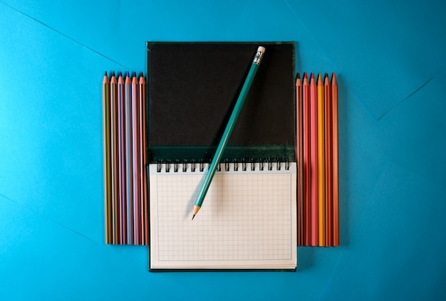 Cahier détachable avec des crayons sur fond de papier bleu pour le texte