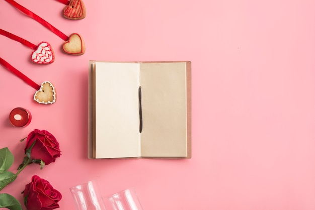 Cahier avec deux roses, deux verres et biscuits