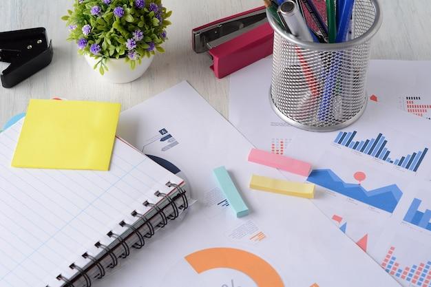Cahier et documents financiers avec des graphiques et des chiffres