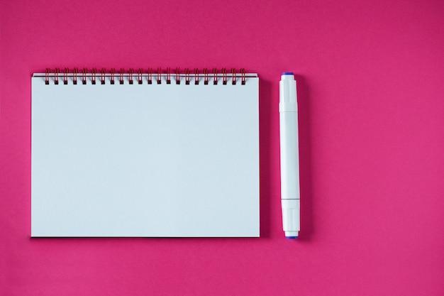 Cahier d'école sur un bloc-notes en spirale rose sur une table. espace copie vue de dessus. bloc-notes de bureau à plat.