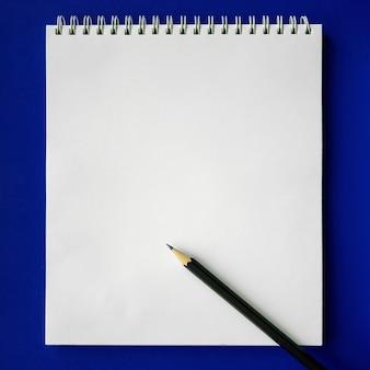 Cahier d'école et crayon sur fond bleu, concept de retour à l'école, éducation élémentaire moderne. mise à plat.