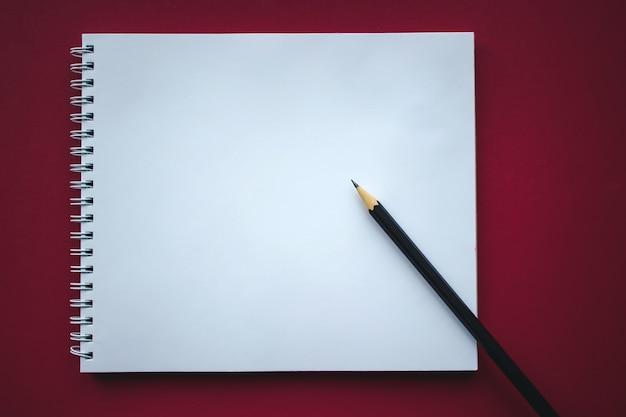 Cahier d'école et crayon sur fond rouge, concept de retour à l'école, éducation élémentaire moderne. mise à plat.