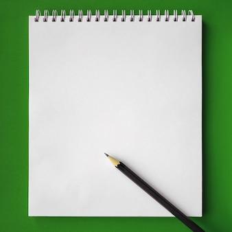 Cahier d'école et crayon sur fond vert, concept de retour à l'école, éducation élémentaire moderne. mise à plat.