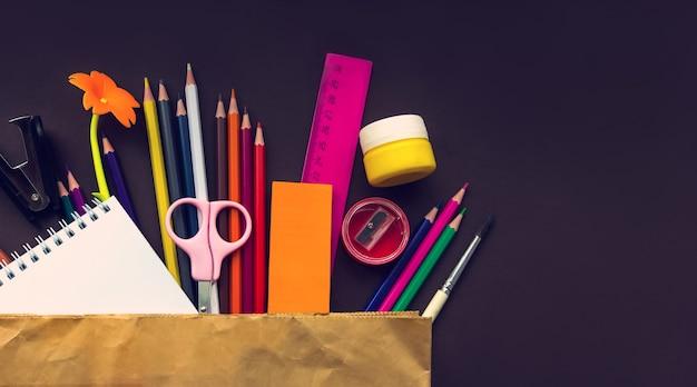 Cahier d'école et divers articles de papeterie dans un sac en papier sur fond marron papeterie de fournitures scolaires