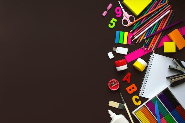 Cahier d'école et divers articles de papeterie avec espace de copie. fournitures scolaires papeterie, crayons de couleur, peintures, papier sur fond marron, concept de retour à l'école, éducation élémentaire moderne. mise à plat.