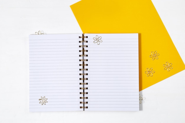 Cahier d'école ouvert au printemps avec des feuilles lignées propres et des clips en métal doré sur un bureau blanc. retour au concept de l'école. vue d'en-haut.