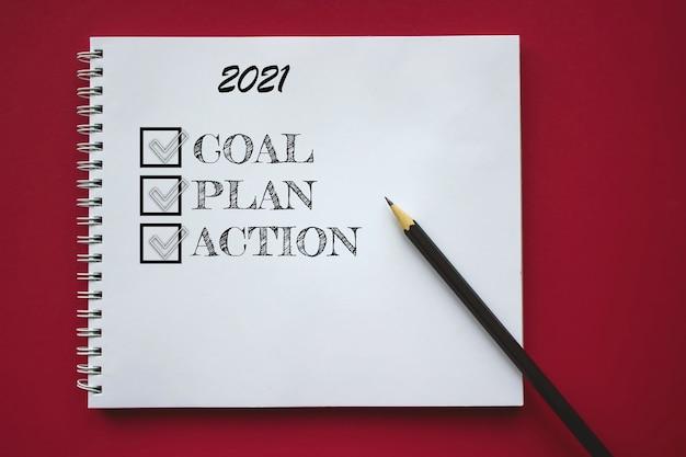 Cahier d'école avec texte objectif, plan et action pour 2021 et crayon sur fond rouge, concept de retour à l'école, éducation élémentaire moderne. mise à plat.