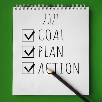 Cahier d'école avec texte objectif, plan et action pour 2021 et crayon sur fond vert, concept de retour à l'école, éducation élémentaire moderne. mise à plat.