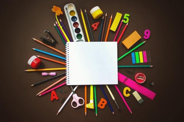 Cahier d'écolier et divers articles de papeterie. retour au concept de l'école. cadre de fournitures scolaires et de bureau.