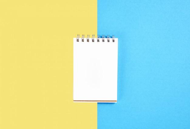 Cahier d'écran blanc vide et stylo placé sur fond jaune et bleu pastel.