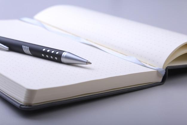 Cahier élégant noir et stylo à bille sur le bureau.