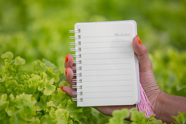 Un cahier entre les mains d'une jeune femme dans la pépinière.