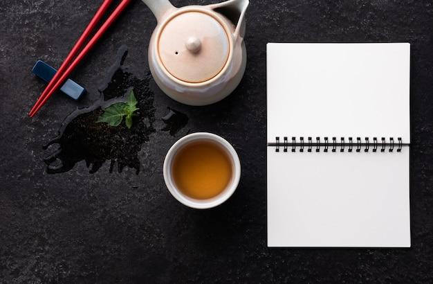 Cahier de l'espace et baguettes rouges avec du thé