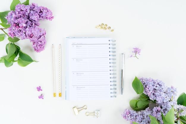 Cahier d'espace de travail de bureau à domicile vue de dessus plat laïque avec des fleurs lilas