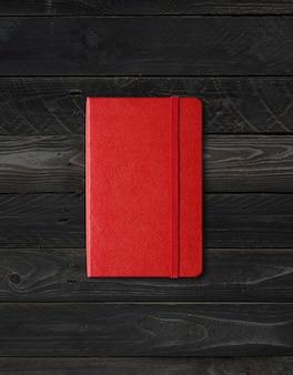Cahier fermé rouge isolé sur fond de bois noir