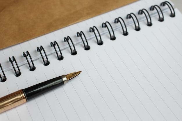 Un cahier avec des feuilles propres, une enveloppe et un stylo doré sur la table