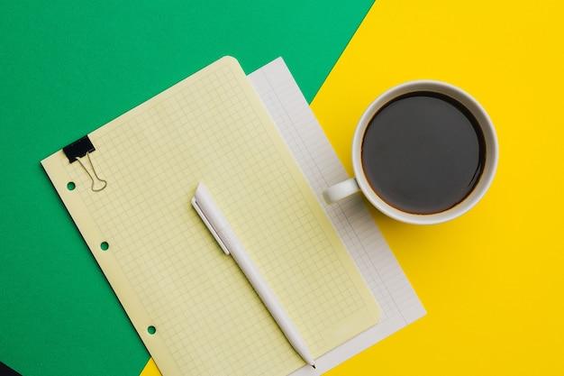 Cahier sur la fleur de stylo de table dans un fond coloré de bureau de travail de pot