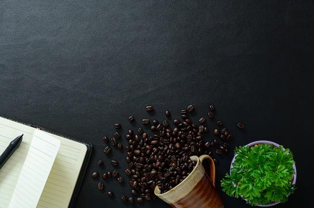 Cahier et grains de café sont placés sur le bureau, vue de dessus