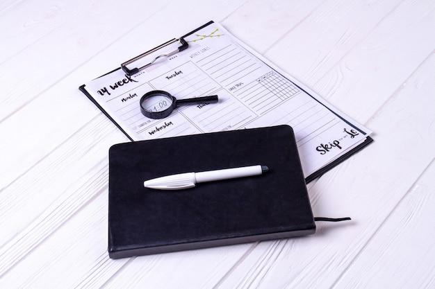 Cahier de gros plan avec stylo blanc et calendrier hebdomadaire. fond de bureau blanc.