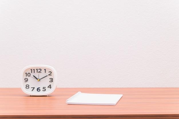 Le cahier et l'horloge sont sur la table.