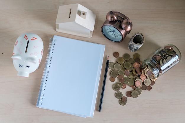 Cahier, horloge, tirelire, modèle de maison et pièce de monnaie. finances et argent concepts d'épargne