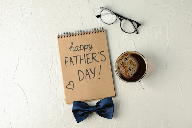 Cahier avec inscription fête des pères heureuse, noeud papillon bleu, tasse de café et verres sur fond blanc