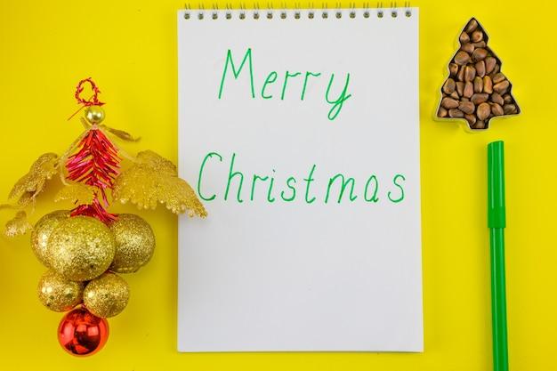 Cahier avec l'inscription joyeux noël sur fond de décorations du nouvel an.