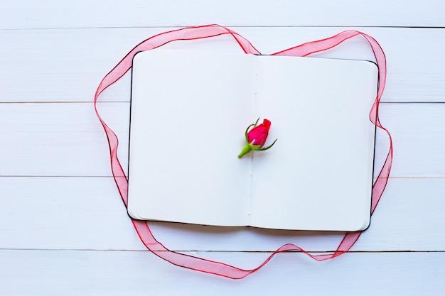 Cahier de journal avec rose et ruban sur un fond en bois blanc. vue de dessus