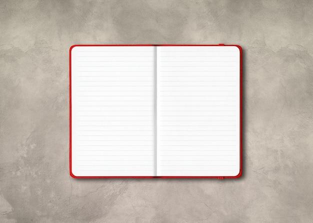 Cahier ligné ouvert rouge isolé sur fond de béton