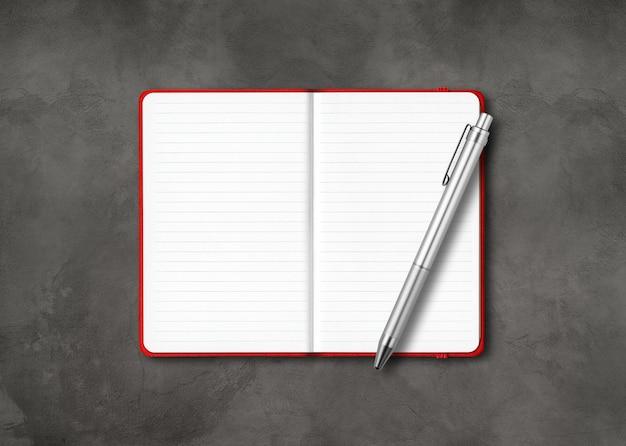 Cahier ligné ouvert rouge avec un stylo isolé sur fond de béton foncé