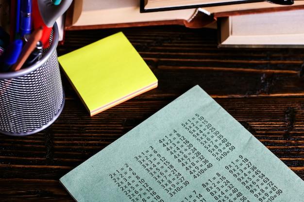 Cahier, livres ouverts et fournitures scolaires sur une table en bois sombre sur fond de craie
