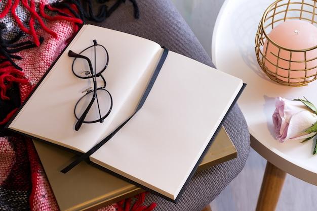 Cahier à lunettes sur un plaid rouge. confort du concept.
