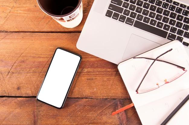 Cahier et lunettes près de gadgets et de mug