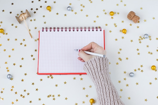 Un cahier et la main d'une femme en pull écrit avec un stylo, des confettis, des étoiles dorées, des rubans, un bouchon de champagne