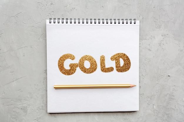 Cahier avec un mot or et un crayon d'or sur gris