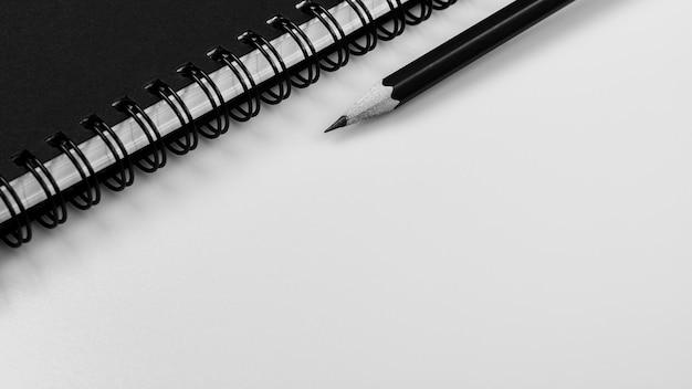 Cahier noir et un crayon sur fond de bureau blanc avec espace de copie