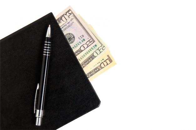 Cahier noir, dollars et stylo sur fond blanc