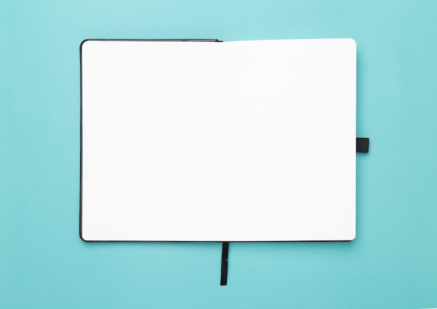Cahier noir ouvert isolé sur fond bleu