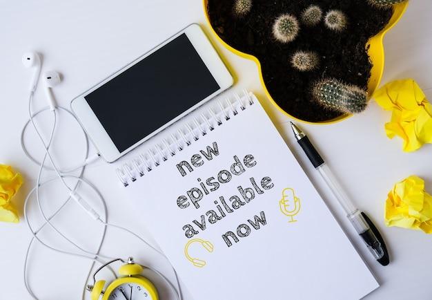 Cahier avec le nouvel episode podcast disponible maintenant en lettrage. écouteurs et téléphone portable. disposition vue de dessus. lieu de travail. livres audio