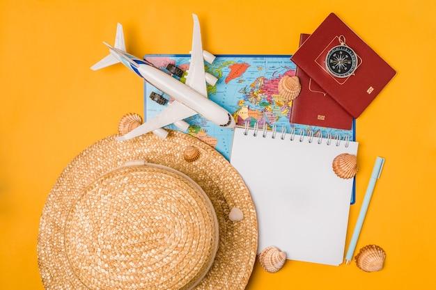 Cahier ouvert avec accessoires de voyage sur fond jaune. planifier les vacances d'été, voyager