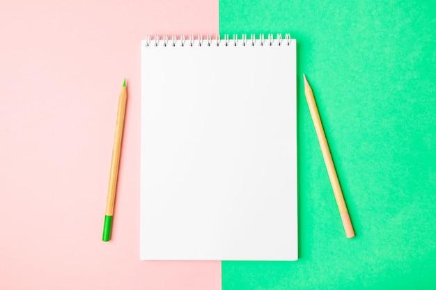 Cahier ouvert blanc sur fond vert et rose. à proximité sont des crayons.